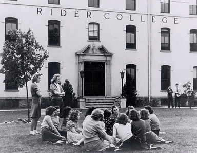 Coeds relaxing outside of the main academic building in Trenton in 1959.